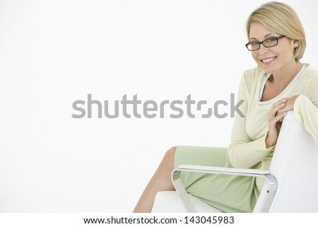 Portrait of happy young businesswoman sitting on modern chair isolated on white background