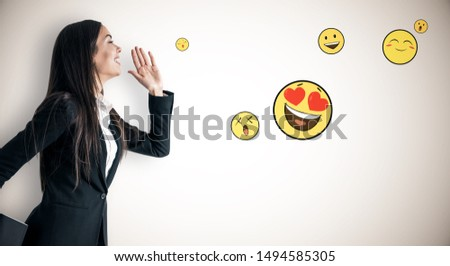 Portrait of happy young businesswoman with emotive on subtle light background. Communication and emotion concept
