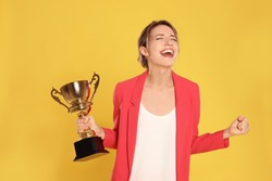 Portrait of happy young businesswoman with gold trophy cup on yellow background