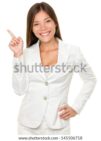Portrait of happy young businesswoman with hand on hip pointing sideways over white background