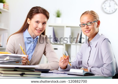Portrait of happy young businesswomen looking at camera in office