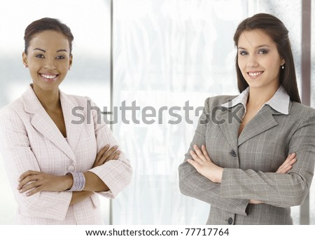 Portrait of happy young businesswomen standing on office corridor, looking at camera, smiling.?