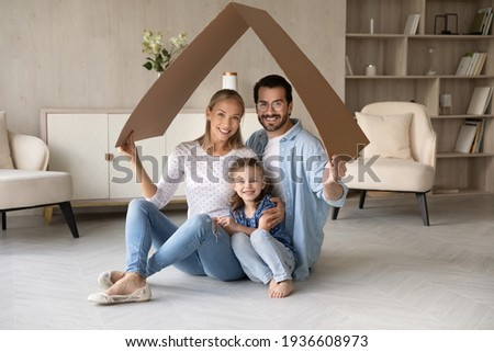 Portrait of happy young Caucasian family with daughter relax under roof celebrate relocation to own home. Smiling parents with girl child enjoy new house or apartment. Rental, real estate concept.
