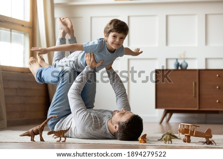 Portrait of happy young Caucasian father lying on floor at home play with cute little 6s son. Loving dad feel playful engaged in funny game activity, hold in hands fly with excited small boy child.