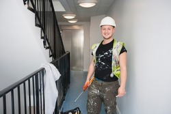 Portrait of happy young construction worker standing by railing