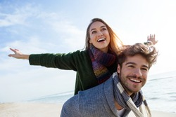 Portrait of happy young couple enjoying the day in a cold winter on the beach.