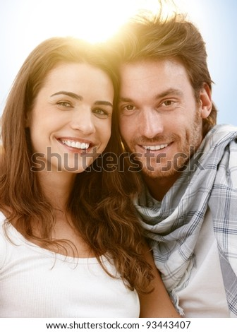 Portrait of happy young couple in summer sunlight, looking at camera, smiling.?