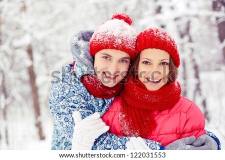 Portrait of happy young couple looking at camera in winter park