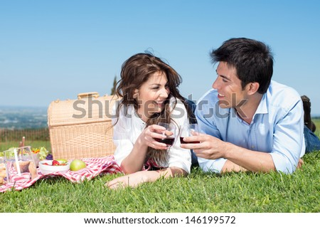 Portrait Of Happy Young Couple Lying On Grass And Enjoying Wine