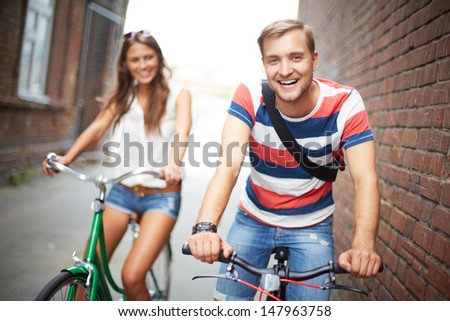 Portrait of happy young couple on bicycles - stock photo