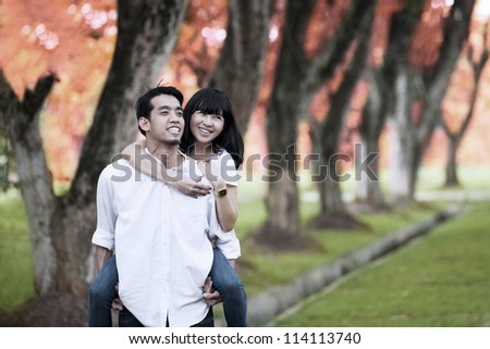 Portrait of happy young couple playing around in the nature on autumn day