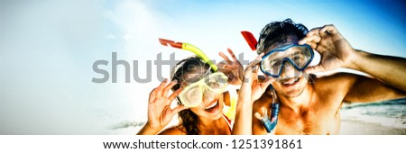 Portrait of happy young couple posing with diving mask on beach #1251391861