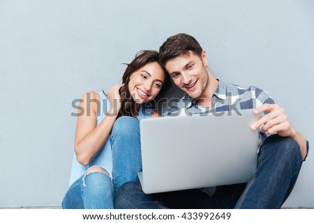 Portrait of happy young couple using laptop isolated on gray background #433992649