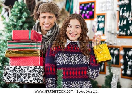 Portrait of happy young couple with Christmas presents standing together at store