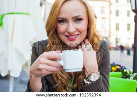 Portrait of happy young cute elegant woman sitting outdoor in a cafe with cup of coffee in a city