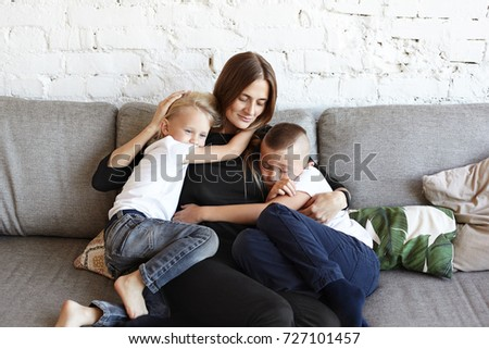 Portrait of happy young European female sitting on grey couch with two little sons who hugging her tight, feeling need of her love and support. Two male siblings sharing attention of their mother Stockfoto ©