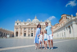 Portrait of happy young family at St. Peter's Basilica church in Vatican city, Rome. Travel parents and kids on european vacation in Italy.
