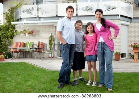Portrait of happy young family standing in front of their house - stock photo