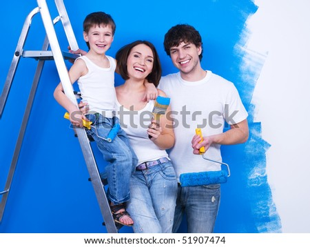 Portrait of happy young family standing together with paintbrush and stepladder - stock photo