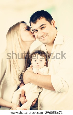 Portrait of happy young family with little child