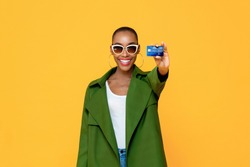 Portrait of happy young fashionable African American woman showing credit card in isolated studio yellow background