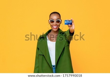 Photo of  Portrait of happy young fashionable African American woman showing credit card in isolated studio yellow background