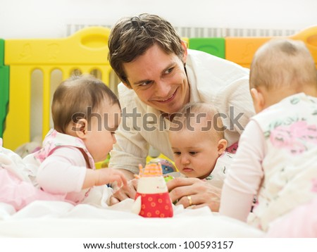 Portrait of happy young father playing with small babies at home