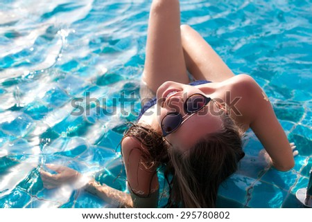 Portrait of happy young female enjoying in the luxury swimming pool. Girl at travel spa resort pool. Summer luxury vacation.