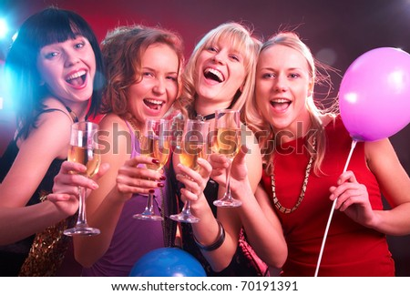Portrait of happy young friends touching the glasses with each other