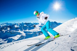 Portrait of happy young girl skiing in the snow with ski in winter time, ski slope and sun in the background.
