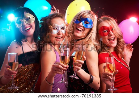 Portrait of happy young girls under masks on the party - stock photo