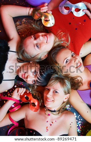Portrait of happy young girls with masks on the party