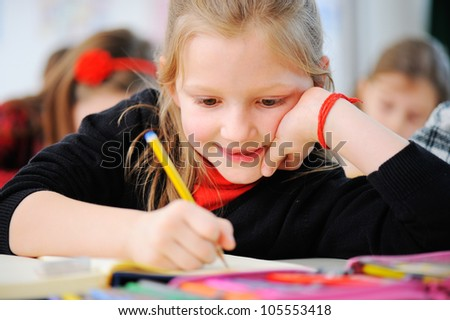 Portrait of happy young girls writing notes in school classroom with friends in background