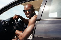 Portrait of happy young guy in his car looking at camera smiling. African male model wearing sunglasses. Muscular man on road trip.