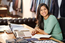 Portrait of happy young Indian atelier owner working on laptop