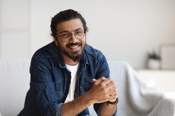 Portrait Of Happy Young Indian Man With Eyeglasses And Dental Braces Posing In Home Interior, Handsome Millennial Western Guy With Beard Smiling At Camera While Relaxing In Living Room, Free Space