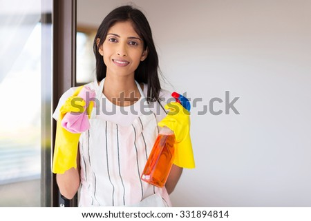 portrait of happy young indian woman doing housework