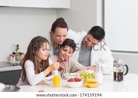 Portrait of happy young kids enjoying breakfast with parents in the kitchen