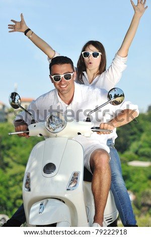 Portrait of happy young love couple on scooter enjoying themselves in a park at summer time