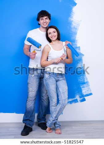 Portrait of happy young loving couple with paintbrushes near the painted wall