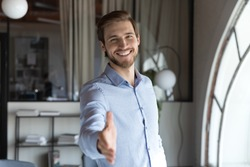 Portrait of happy young male hr stretching hand inviting you spectator to join corporate team, friendly capable manager looking at camera extending hand for handshake welcoming new client or colleague