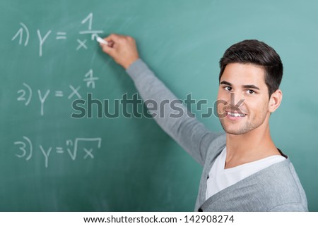 Portrait of happy young male student solving sums on chalkboard in classroom