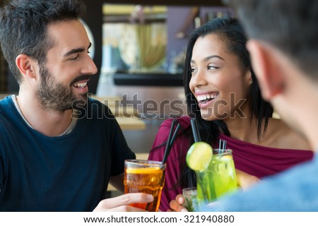 Portrait of happy young man and woman holding cocktail glasses. Friends drinking an alcoholic beverages at bar. Smiling young man and woman drinking juice and smiling. Aperitif time.