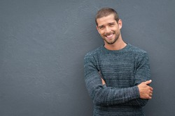 Portrait of happy young man leaning against wall isolated on grey background with big smile. Cheerful guy in winter clothes on gray wall looking at camera. Happy man wearing sweater with copy space.
