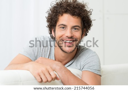 Portrait Of Happy Young Man Sitting On Sofa