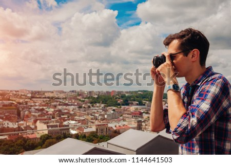 Portrait of happy young man, tourist with camera taking pictures of old city Lviv from viewpoint.
