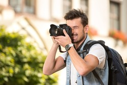 Portrait of happy young man, tourists with camera in the city.