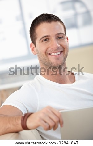 Portrait of happy young man using laptop at home.?