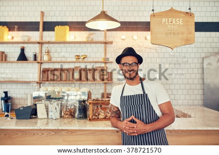 Portrait of happy young man wearing an apron and hat leaning to a cafe counter. Male barista standing at coffee shop looking at a camera and smiling.