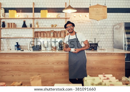Portrait of happy young man wearing an apron and hat standing at a cafe counter holding a cup of coffee. Coffee shop owner looking at a camera and smiling.